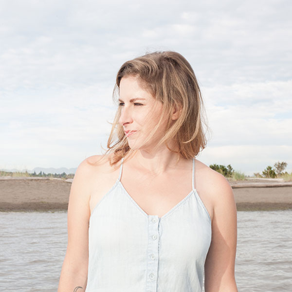 Leah Abramson in the summer wearing a denim tank dress staring to the left, water and shore behind her. Photography by Angela Fama
